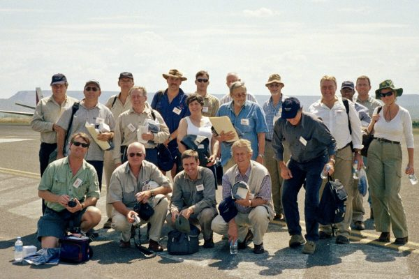 Delegates to the World Diamond Conference field trip at the Argyle diamond mine airstrip in Western Australia.  2003 n/k is not known.  Rear Row L-R: n/k, Keith Goode (resources journalist), n/k, Mike Milligan (De Beers), James Picton (WH Ireland, UK Brokers), Ewan Tyler (geologist associated with the original Argyle discovery), rest n/k. Middle Row: Kevin Hart (Striker Resources NL), Stuart Vercoe (geologist, led the Australian De Beers exploration team in Australia), Vicki Stamoulis (geologist with the South Australian mines department), rest n/k. Bottom Row: n/k, John Bristow (geologist), Jim Richards (geologist), Bill DuChatel (geologist, Ashton Mining)